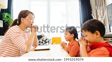 Family praying and worship to GOD with church online sunday service.Live Church with bible.Mother kid sibling praying on holy bible study at home.Lockdown worship.Christian faith hope.Online church.