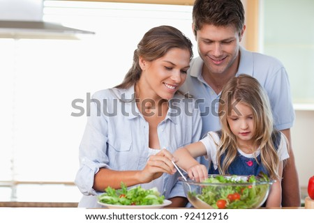 Family preparing a salad in their kitchen