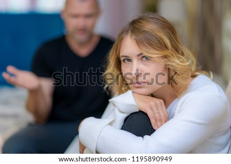 Family problems of the young wife and husband on the sofa. They are sitting in a room right in front of the camera, looking unhappy. Stock photo ©