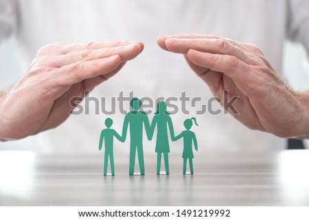 Family protected by hands - Concept of life insurance