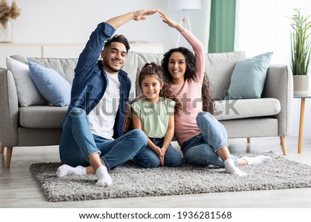 Family Protection. Mom And Dad Making Roof Of Hands Above Their Daughter