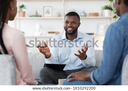 Family Psychotherapy. Friendly Black Therapist Consulting African American Couple At His Office, Selective Focus On Counselor