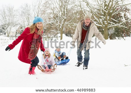 Family Pulling Sledge Through Snowy Landscape