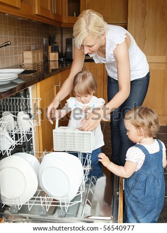 Family put dishes in the dishwasher in the kitchen