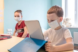 Family quarantine, self isolation. Lockdown and School Closures, Coronavirus Outbreak. Schoolchildren with Face Mask Watching Online Education Class Remote. Studying at Home During COVID-19 Pandemic