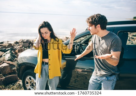 Family quarrel near the car. Scandal and disagreement concept. Crisis in the family. Husband screams at his wife. Couple wants a divorce.