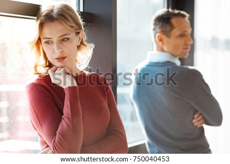 Family quarrel. Nice unhappy young woman standing together and turning away from each other while having a quarrel