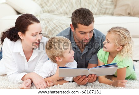 Family reading a book together lying on the floor at home