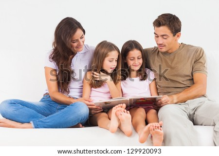 Family reading a story on a sofa in the living room