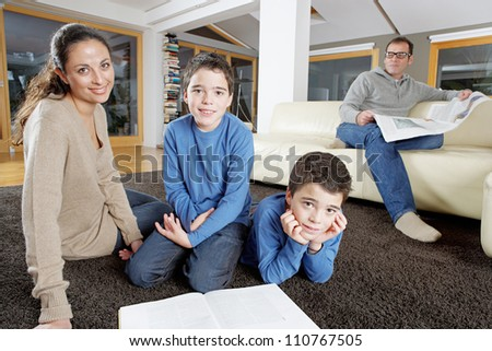Family reading in living room on Sunday, looking at the camera and smiling.