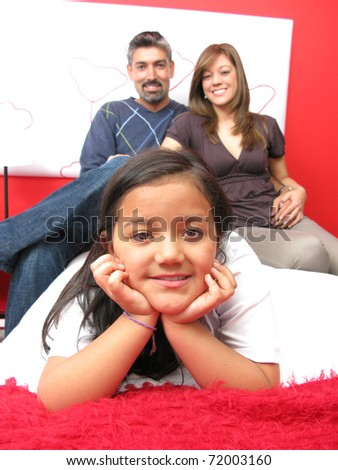 Family reclining in bed smiling at camera