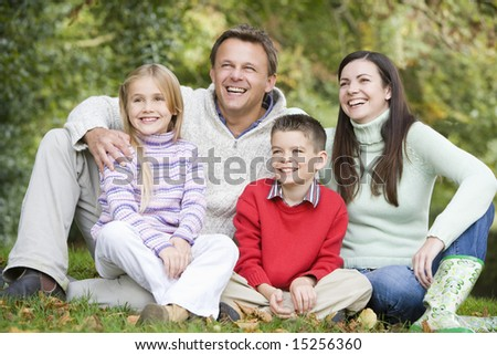Family relaxing in autumn woods