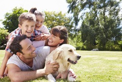 Family Relaxing In Garden With Pet Dog