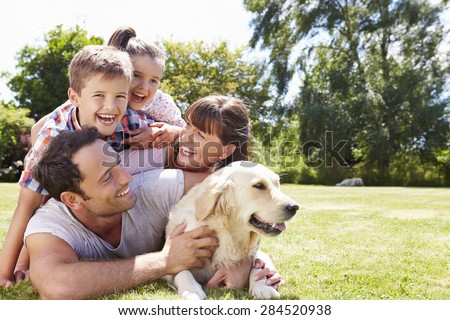 Family Relaxing In Garden With Pet Dog #284520938