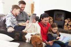 Family Relaxing Reading Book And Using Digital Tablet