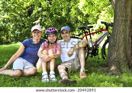 Family resting in summer park with bicycles