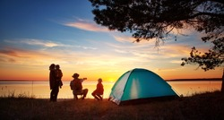 Family resting with tent in nature at sunset. Woman, man and children near seaside