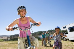 Family riding bikes in countryside on motor home vacation