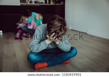 family rivalry-crying sad child and mother holding other kids #1183419901