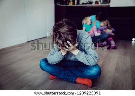family rivalry-crying sad child and mother holding other kids #1209225091