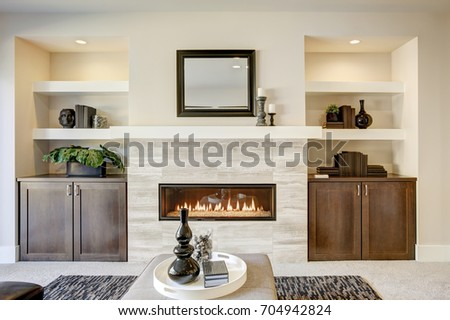 Family room design with traditional fireplace framed by built in shelves and cabinets. Northwest, USA #704942824