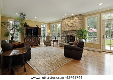 Family room in luxury home with stone fireplace stock for Luxury fireplaces luxury homes