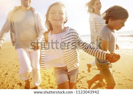 Family running on sandy beach at sunset