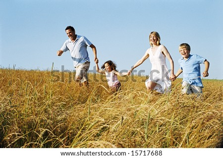 Family running outdoors holding hands smiling