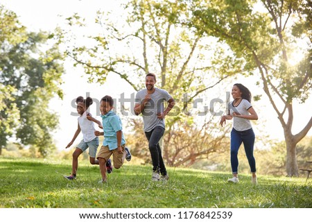 Family Running Through Park Together