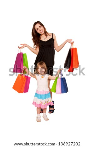 Family shopping. Two sisters, a teenager and a little girl holding up shopping bags and smiling. Holidays and gifts concept. Isolated on white background
