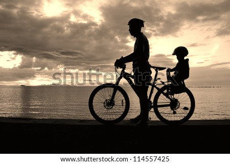Family silhouette , daughter on child seat with parent at the beach at sunset.