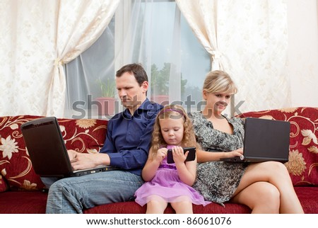 family sits on a sofa everyone about the the computer.