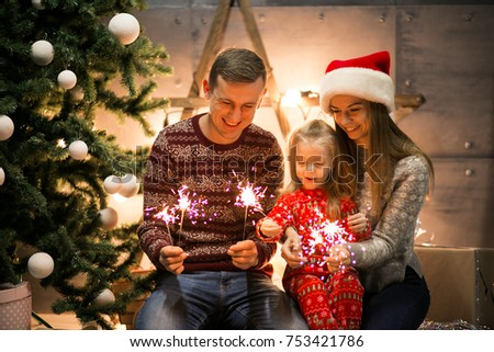 Family sitting by the Christmas tree with bengal lights #753421786