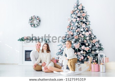 family sitting near Christmas tree and fireplace. boy sits on rocking horse. studio. #1527595319