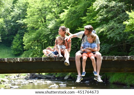 Family sitting on a bridge crossing mountain river
