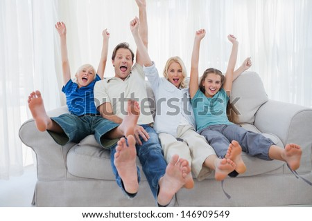 Family sitting on a couch and raising arms while watching television