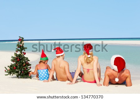 Family Sitting On Beach With Christmas Tree And Hats