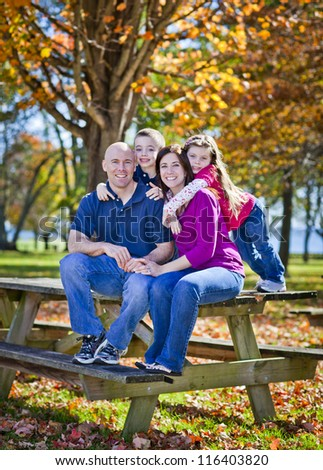 Family sitting on bench during the fall