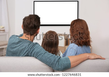 Family sitting on couch and watching TV at home, space for design on screen. Leisure and entertainment