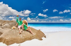 Family sitting on rock on beautiful Anse Intendance beach, young couple in green with three year old toddler boy. Summer vacation at Seychelles, Mahe.