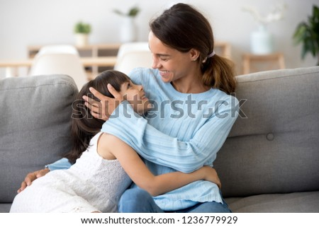 Family sitting on sofa at home young single mother looking at daughter with love and tenderness showing support and devotion. Happy motherhood friendly relationship between mommy and kid best friends