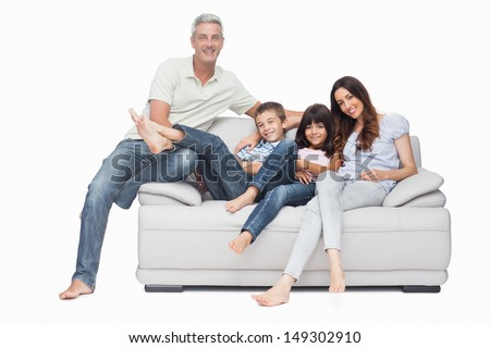 Family sitting on sofa smiling at camera on white background