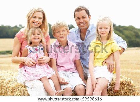Family Sitting On Straw Bales In Harvested Field