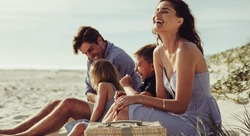 Family sitting on the beach and smiling. Woman with her family relaxing on the seashore and laughing.
