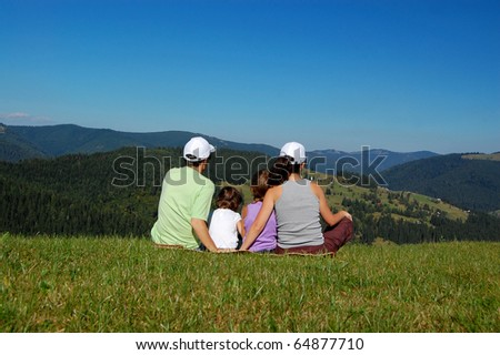 Family sitting on the grass and looking at the beautiful mountain view