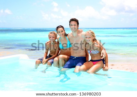 Family sitting on the side of an infinity pool