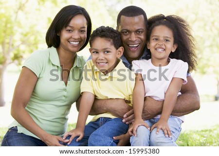 Family sitting outdoors smiling