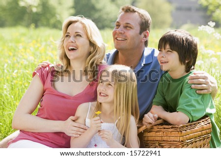 Family sitting outdoors with picnic basket smiling