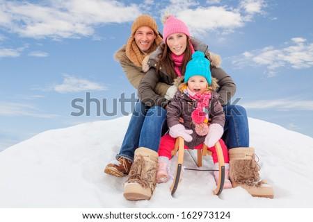 family sliding winter couple enjoying season