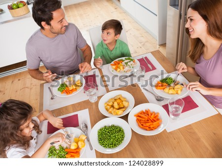 Family smiling around a healthy meal in kitchen